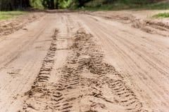 Däckmönsterfläckar på den torra lantliga sandiga vägen Royaltyfri Foto