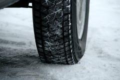 Däckmönsterkvarter för insnöat gummihjul på bilen på den snöig landsvägen Arkivfoton
