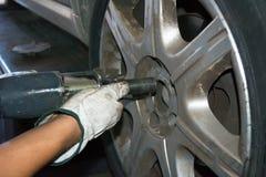 Däckreparatör som fixar ett hjul genom att använda en inverkanskiftnyckel royaltyfri fotografi