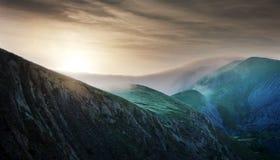 Dämmern Sie über den Hügeln, die mit dichtem Nebel bedeckt werden Stockfotografie
