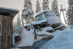Dämmerung über einer Planierraupe bedeckt mit Schnee Stockfotografie