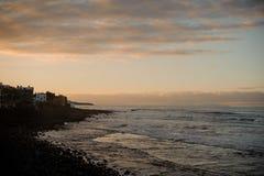 Dämmerung über Küste der alten Stadt und des Meeres mit Wellen unter dem Himmel stockfotografie