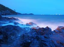 Dämmerung an den Küstenfelsen und -wellen lizenzfreies stockfoto