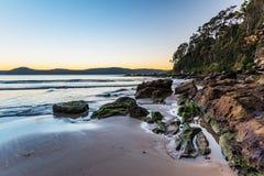 Dämmerung am Strand mit Felsen stockfoto