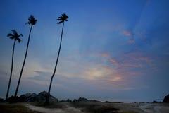 Dämmerungansicht des Sandstrandes mit Felsen Lizenzfreies Stockbild