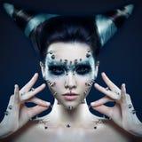 Dämonmädchen mit Spitzen auf dem Gesicht und dem Körper Stockfoto