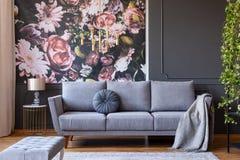 Dämpa och filt på en stilfull soffa i en grå vardagsruminre med murgrönaväxten, och blommor skrivar ut på väggen arkivbild