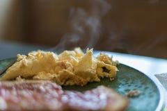 Dämpfende heiße Eier auf einer grünen Platte mit dem Toast undeutlich im Vorderteil Stockfotos