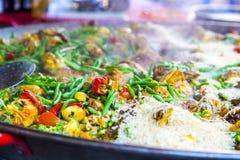 Dämpfende heiße Paella, Meeresfrüchte, Reis und Gemüse im französischen Kennzeichen lizenzfreie stockfotografie