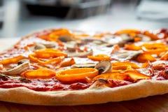 Dämpfende heiße Pizza mit orange Pfeffern, Schinken und Pilzen lizenzfreie stockfotografie