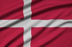 Dänemark-Flagge wird auf einem Sportstoffgewebe mit vielen Falten dargestellt Sportteamfahne stockfotos