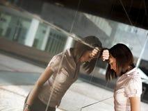 Dängande huvud för frustrerad kvinna mot väggen Arkivbilder