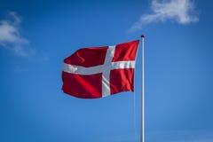 Dänische Flagge im Sonnenschein gegen blauen Himmel mit den Wolken, horizontal Stockfotos