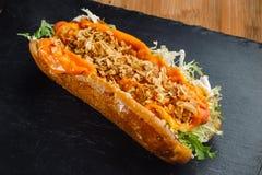 Dänische Hotdoge auf schwarzem Schiefer Stockbilder