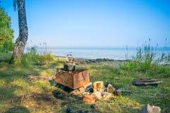 Däst teakettle på en brand på en bank av en sjö - fotvandra landskapet, Uveldy, Royaltyfria Foton