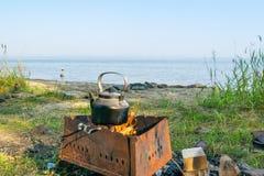 Däst teakettle på en brand på en bank av en sjö - fotvandra landskapet, Uveldy, Arkivfoto