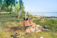 Däst teakettle på en brand på en bank av en sjö - fotvandra landskapet, Uveldy, Royaltyfri Fotografi