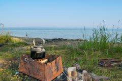Däst teakettle på en brand på en bank av en sjö - fotvandra landskapet, Uveldy, Fotografering för Bildbyråer