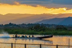 Długiego ogonu czółno pełno turyści świszczy szybko na Inle jeziorze, Myanmar fotografia stock