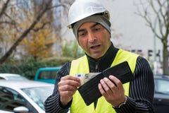 Dålig överraskning: byggnadsarbetare och hans tomma plånbok Arkivbild