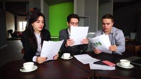 Dålig dag på arbete för män och kvinnor av anställda för företags` s och arbete med dokument, på tabellen med grejer i konferens arkivfilmer