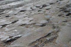 Dålig gammal sprucken skadad asfalt royaltyfri bild