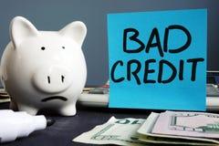 dålig kreditering Olycklig spargris och räknemaskin arkivfoto
