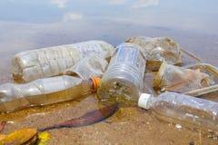 Dålig miljö- vana av felaktigt förfogande av icke-biologiskt nedbrytbar PVC-koppar och flaskor i en sjö Selektivt fokusera royaltyfri foto
