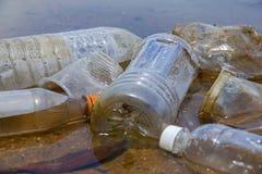 Dålig miljö- vana av felaktigt förfogande av icke-biologiskt nedbrytbar PVC-koppar och flaskor i en sjö Selektivt fokusera royaltyfri bild