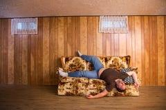 Dålig sömn på en soffa fotografering för bildbyråer