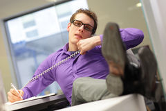 Dålig sammanträdeställing - affärsman i hans kontor på telefonen royaltyfria foton