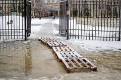 Dålig väg till skolan, träpaletter på en pöl arkivbild