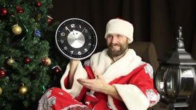 Dåliga brutala Santa Claus le och shower klockan, fem minuter till tolv, på bakgrunden av julgranen stock video