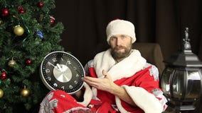 Dåliga brutala Santa Claus le och shower klockan, fem minuter till tolv, på bakgrunden av julgranen arkivfilmer