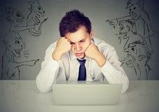 Dåliga onda män som pekar på stressat grabbsammanträde på tabellen med bärbar datordatoren fotografering för bildbyråer