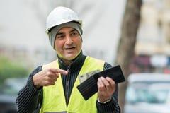 Dåliga tider: fattig byggnadsarbetare och hans tomma plånbok Fotografering för Bildbyråer