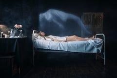 Dåligt kvinnan som ligger i sjukhussäng, andasidor, förkroppsligar royaltyfria foton