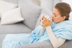 Dåligt kvinnasammanträde på soffan med koppen av drycken Arkivbild