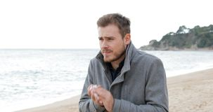 Dåligt man som hostar i en kall dag på stranden lager videofilmer