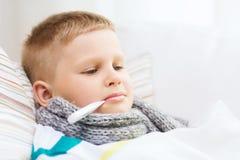 Dåligt pojke med hemmastadd influensa arkivfoto