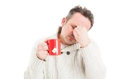 Dåligt rånar hållande te för mannen och lidande en migrän Royaltyfria Bilder