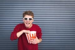 3D玻璃的疯狂的年轻人吃玉米花杯子和看照相机的反对黑暗的背景 库存照片