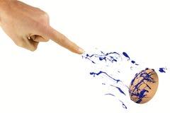 La mano rocía color azul en el huevo Fotografía de archivo