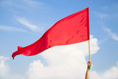 Dé agitar una bandera roja con el cielo azul Fotos de archivo libres de regalías