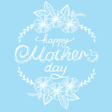 Dé a caligrafía el día de madre feliz blanco con las flores y las hojas en un fondo azul Postal de la vendimia Foto de archivo libre de regalías