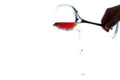 Dé a controles al vidrio con el vino que fluye abajo aislado de un blanco Fotos de archivo libres de regalías
