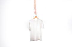 Dé a controles una camiseta blanca de una suspensión en un fondo blanco Imágenes de archivo libres de regalías
