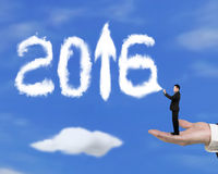 Dé detener al hombre de negocios que rocía la flecha 2016 encima de las nubes con el cielo Foto de archivo libre de regalías