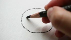 Dé a dibujo la cara sonriente con el lápiz de carbón de leña en el papel blanco de la lona almacen de metraje de vídeo