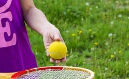 Dé el atleta con una pelota de tenis en fondo de la hierba verde Fotos de archivo